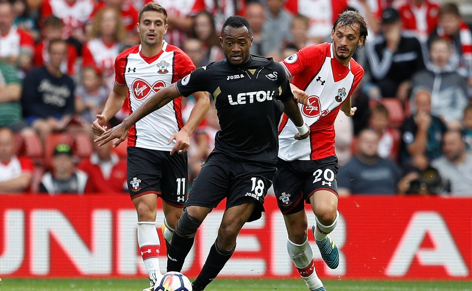 Swansea City's Jordan Ayew in action with Southampton's Dusan Tadic and Manolo Gabbiadini. Southampton were held by Swansea City to a goalless draw in Mauricio Pellegrino's first competitive match in charge of the Saints.