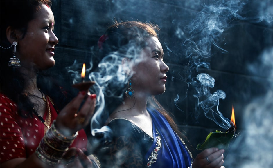 Women offering prayers are seen amid incense smoke at the Pashupatinath temple during Teej celebrations in Kathmandu. The festival culminates in 'Rishi Panchami' where women break their fast after performing the 'Sapta Rishi Puja'. AP