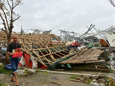 A man carries belongings away from a destroyed structure after a typhoon in Xiamen in southeastern China's Fujian province. AP