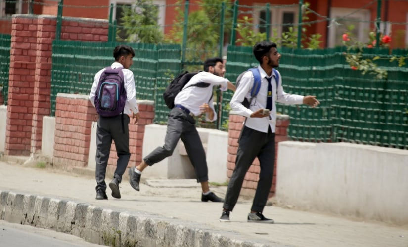 A student throws a rock at the security forces during clashes in Srinagar. Firstpost/Suhail Bhat