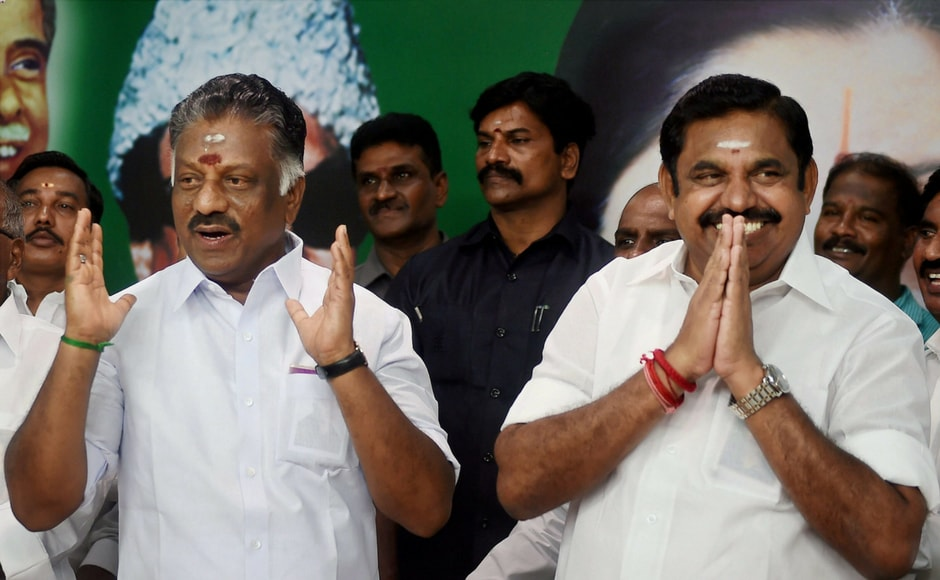 Chief Minister K Palaniswamy (R) and O Panneerselvam exchange greetings with supporters following merger of their factions in Chennai on Monday. According to Palaniswamy, AIADMK's first priority will be to revive the two-leaves symbol. PTI