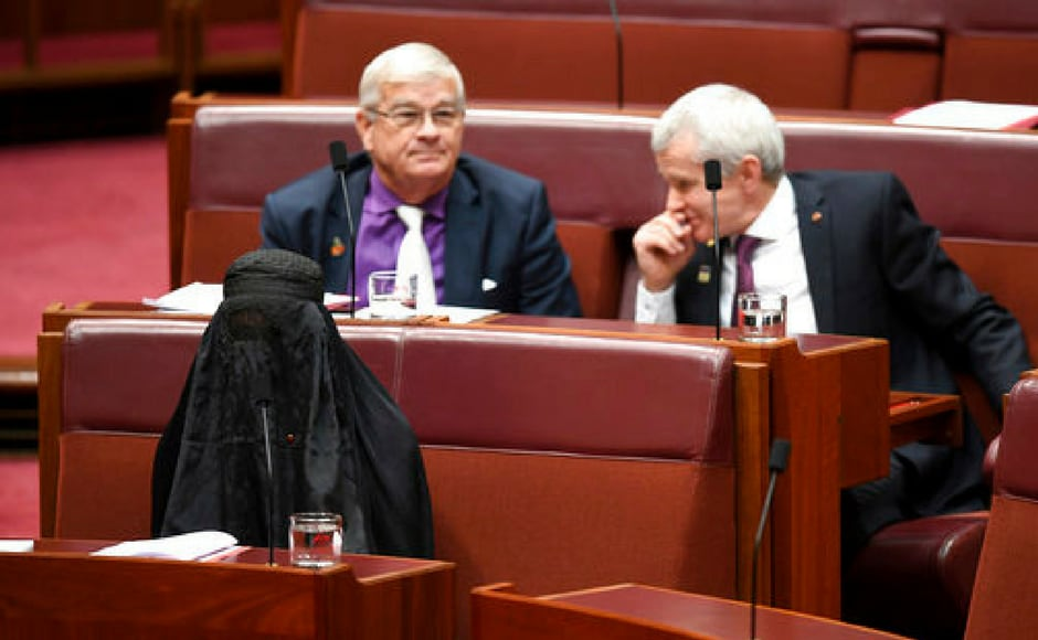 Senator Pauline Hanson, bottom left, wears a burqa during question time in the Senate chamber at Parliament House in Canberra, Australia on Thursday. Hanson, leader of the anti-Muslim, anti-immigration One Nation minor party, sat wearing the black head-to-ankle garment for more than 10 minutes before taking it off as she rose to explain that she wanted such outfits banned on national security grounds. AP