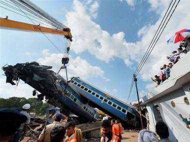 A mangled coach being hauled off the tracks. PTI