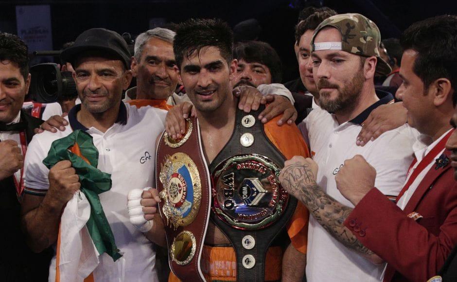 Vijender Singh, centre, celebrates after winning the double title against WBO Oriental Super Middleweight champion of China Zulpikar Maimaitiali. AP