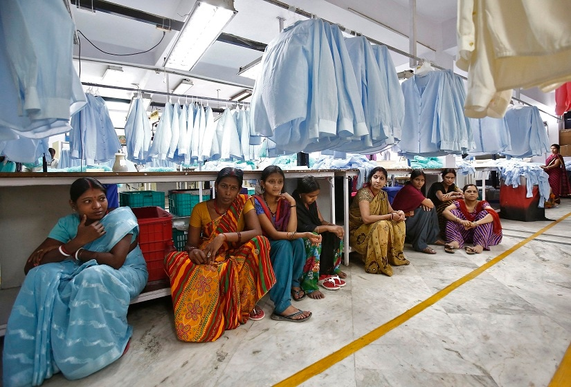 Employees sit during their lunch time inside a textile mill of Orient Craft Ltd. at Gurgaon in Haryana, northern India April 16, 2014. When Narendra Modi talks about creating jobs in labour-intensive manufacturing, textile entrepreneur Sudhir Dhingra hopes the Indian opposition leader means business. Dhingra, who employs 30,000 workers in more than 20 factories around the capital New Delhi, says that politicians - for all their promises - have shown no interest in acting to avert a looming employment crisis. Early on, Dhingra survived a change of fashion that saddled him with a pile of unsold stock. Learning his lessons - to keep close tabs on the market and control costs - he built Orient Craft into $250 million business making 200,000 garments daily. Picture taken April 16, 2014. REUTERS/Anindito Mukherjee (INDIA - Tags: BUSINESS POLITICS ELECTIONS EMPLOYMENT TEXTILE) - RTR3NRZ0