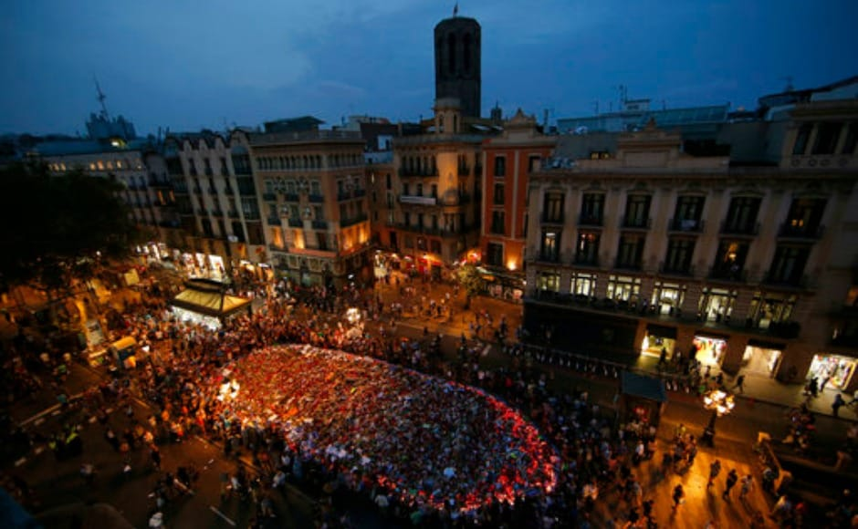 People stand around the memorial of flowers, messages and candles after the demonstration ended. The march concluded at Plaza de Catalunya near Las Ramblas. AP