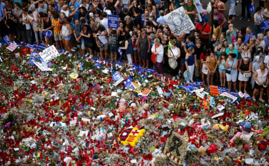 """People gather next to candles and flowers placed on the ground in Las Ramblas following the demonstration. The slogan of the demonstration was """"no tinc por,"""" which translates to """"not afraid"""" in Catalan. AP"""
