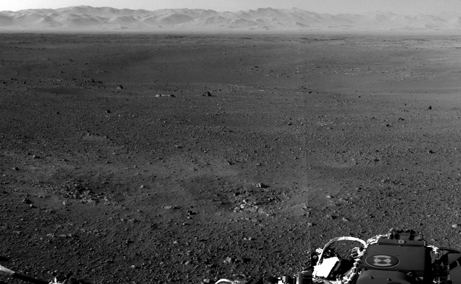 This is the first image beamed back from mars. In the distance, the rim of the Gale crater can be seen. Image: NASA.