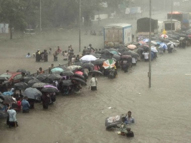 People stuck in waterlogged streets of Mumbai on Tuesday. PTI