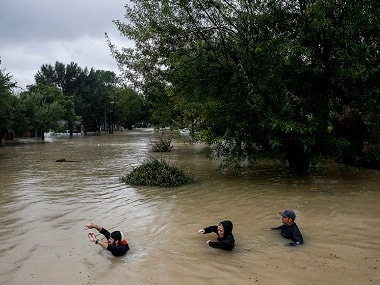 People wade through chest deep water due to constant rain from Hurricane  Harvey. AP