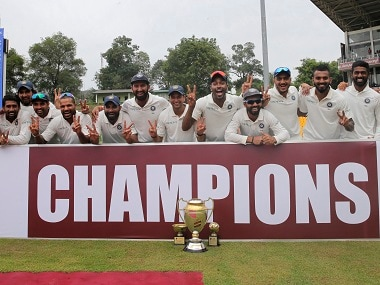 Members of the Indian cricket team pose with the winners trophy. AP