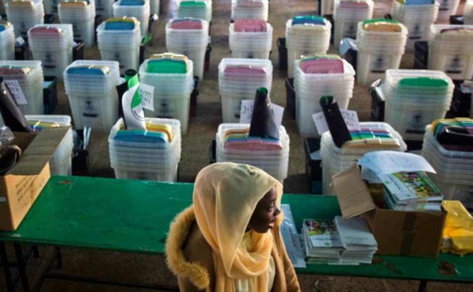 A Kenyan election volunteer walks past ballot boxes and electoral material to be distributed to various polling stations in Nairobi, Kenya, Monday, Aug. 7, 2017. Kenyans are due to go to the polls on Aug. 8. to vote in a general election after a tightly-fought presidential race between President Uhuru Kenyatta and main opposition leader Raila Odinga. (AP Photo/Jerome Delay)