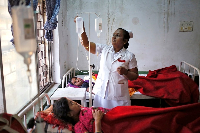 "A nurse tends to a woman, who underwent a sterilization surgery at a government mass sterilisation ""camp"", at Chhattisgarh Institute of Medical Sciences (CIMS) hospital in Bilaspur, in the eastern Indian state of Chhattisgarh, November 13, 2014. The doctor whose sterilisation of 83 women in less than three hours ended in at least a dozen deaths said on Thursday the express operations were his moral responsibility and blamed adulterated medicines for the tragedy. Dr R. K Gupta, who says he has conducted more than 50,000 such operations, denied that his equipment was rusty or dirty and said it was the government's duty to control the number of people that turned up at his family-planning ""camp"". REUTERS/Anindito Mukherjee (INDIA - Tags: HEALTH CRIME LAW SOCIETY) - RTR4DYNZ"