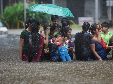 People walk through a flooded street during heavy rains in Mumbai. PTI