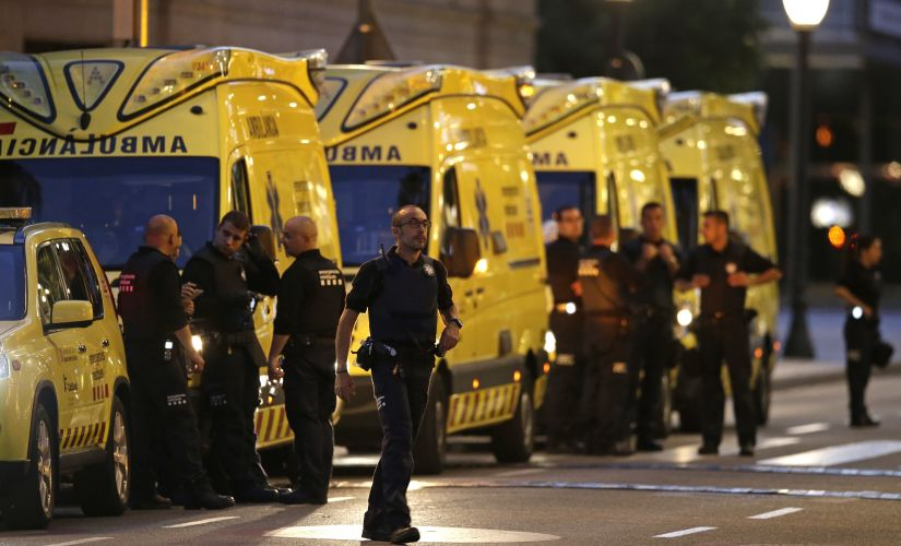 Emergency workers in Barcelona stand guard on a blocked street on Thursday after the terror attack. AP