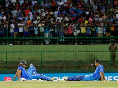 Rohit Sharma and MS Dhoni rest as they wait for the game to resume after some spectators threw plastic bottles into the ground. AP