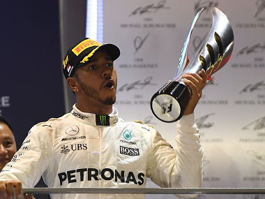 Lewis Hamilton celebrates on the podium after winning the Singapore Grand Prix. AFP