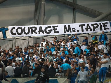"Om's fans cheer next to a banner reading ""Be brave M. Tapie"" in tribute to OM's former president hospitalized in Paris, prior to the French L1 football match Olympique de Marseille vs Toulouse on September 24, 2017 at the Velodrome stadium in Marseille, southern France. / AFP PHOTO / BERTRAND LANGLOIS"