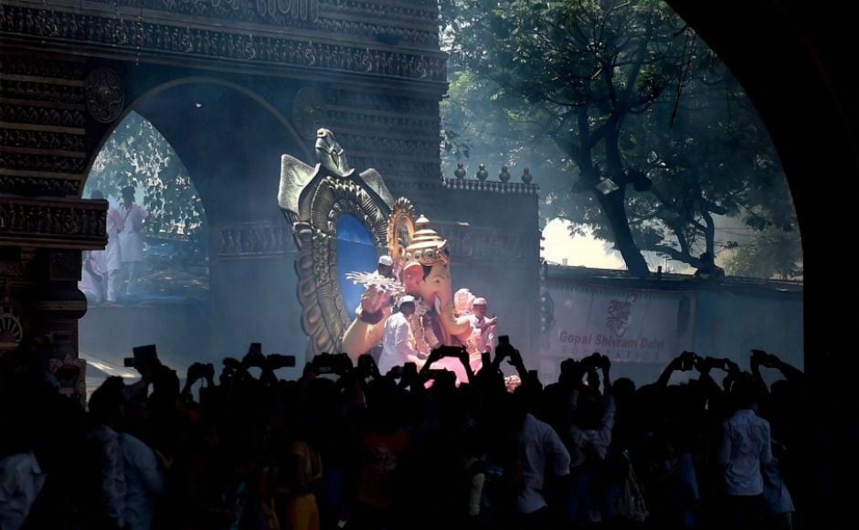 """The idols were brought onto the roads accompanied by the beats of <em>dhols</em>(drums) and cymbals, thousands dancing and chanting """"Ganpati Bappa Moraya, Pudhchya Varshi Lavkar Ya"""" (Lord Ganesha bless us, come soon next year), in clouds of auspicious red 'gulaal'. PTI"""