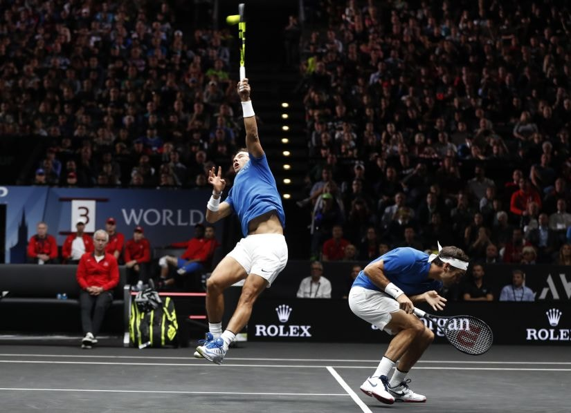 Roger Federer, right, crouches as his teammate Rafael Nadal, left, returns a ball during their doubles match. AP