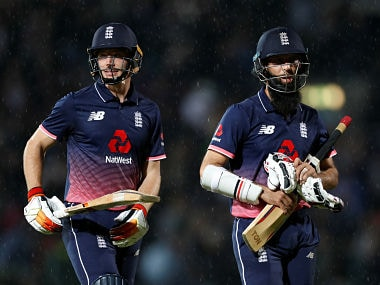 England's Moeen Ali and Jos Buttler walk off due to a rain delay. Reuters