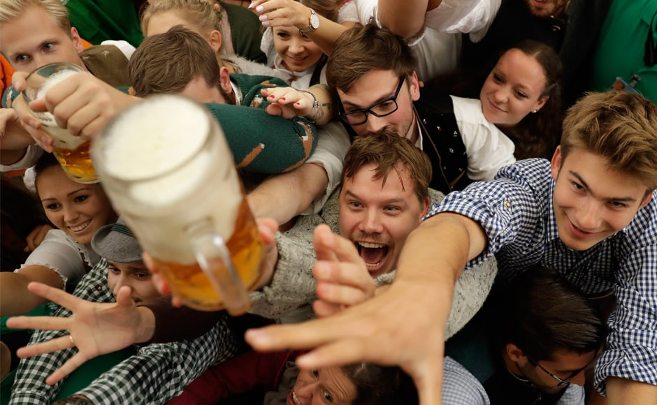 Youngsters reach out for more beer on the opening day of the 184th Oktoberfest festival in Munich, Germany, on Saturday. The world's largest beer festival will be held from 16 September to 3 October. AP