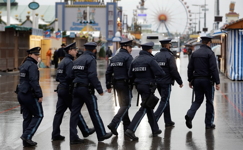 Police officers conduct patrolling during heavy rain prior to the opening of Oktoberfest. Revelers also faced increased security precautions due to possible attacks. AP