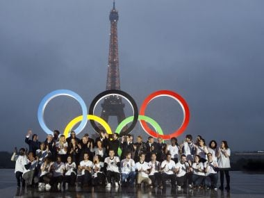 Paris officials pose in front of a display showing the Olympic rings on Trocadero plaza that overlooks the Eiffel Tower on Wednesday. AP
