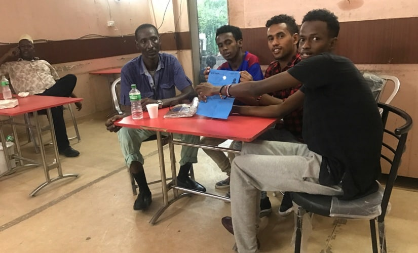 Refugees from Somalia, who manage an Arabic restaurant in Khirki village, flash the UNHCR blue card, the only identity proof for a refugee in India. Firstpost/Pallavi Rebbapragada