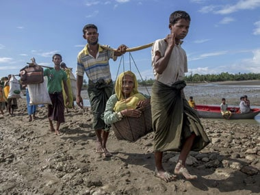 Rohingya Muslims, who crossed over from Myanmar into Bangladesh, carry an elderly woman in a basket and walk towards a refugee camp in Shah Porir Dwip, Bangladesh on Thursday. AP/PTI