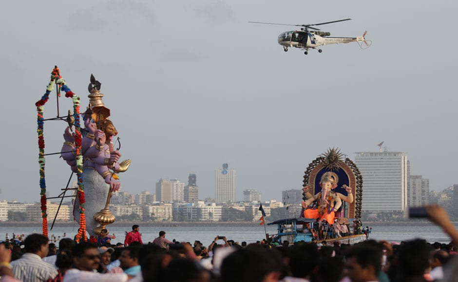 "The idols were brought onto the roads to the accompaniment of 'dhols' (drums), cymbals, thousands dancing and chanting ""Ganpati Bappa Moraya, Pudhchya Varshi Lavkar Ya"" (Lord Ganesha bless us, come soon next year), in clouds of auspicious red 'gulaal'. Image courtesy Sachin Gokhale/Firstpost"