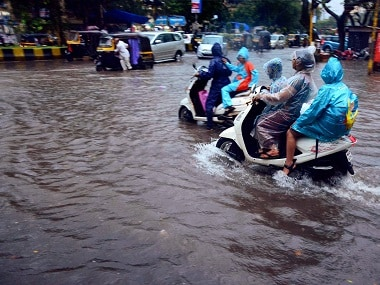 Vehicles wade through a flooded road in Mumbai. PTI