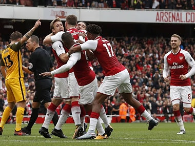 Arsenal's Nacho Monreal celebrates with teammates after scoring the team's first goal. AFP