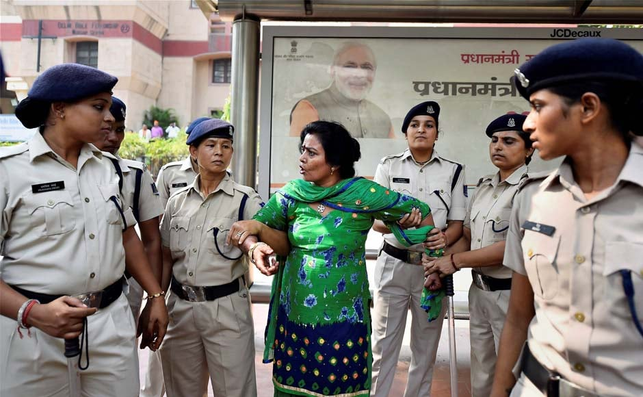 Police apprehend a Delhi BJP woman worker during the rally outside the CPM office in New Delhi on Monday. PTI