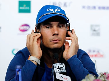Rafael Nadal of Spain puts on a headset during a news conference of the China Open tennis tournament at the Diamond Court in Beijing, Monday, Oct. 2, 2017. (AP Photo/Andy Wong)