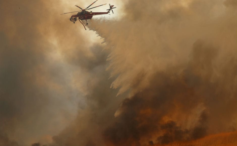 Firefighting helicopters dropped water onto burning homes as a wind-driven fire tears through neighbourhoods in Anaheim Hills. About 20,000 people have been evacuated from their homes by Monday, and additional evacuation too was carried out in several counties. Reuters