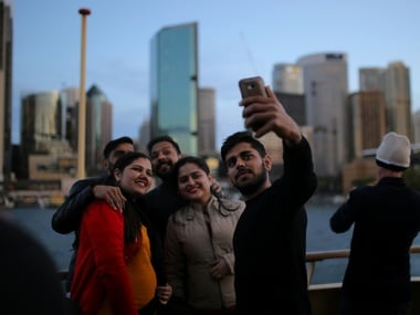 A group of tourists aboard the Manly ferry take a group selfie. Reuters