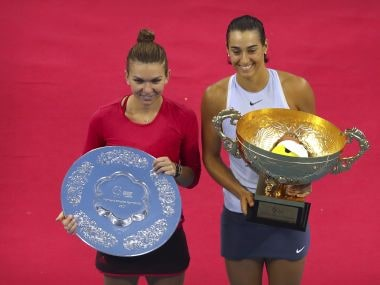 Simona Halep of Romania, left, and Caroline Garcia of France pose with their trophies after their women's singles championship match in the China Open tennis tournament at the Diamond Court in Beijing, Sunday, Oct. 8, 2017. (AP Photo/Mark Schiefelbein)
