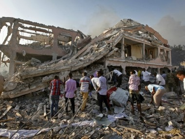 People gather and search for survivors by destroyed buildings at the scene of a blast in Mogadishu. AP