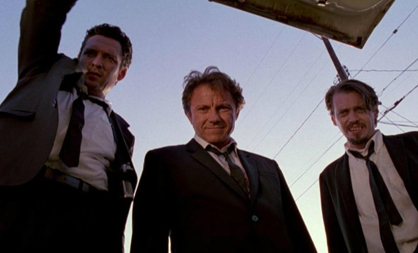 Michael Madsen, Harvey Keitel and Steve Buscemi gaze down upon officer Marvin Nash (played by Kirk Baltz), who is tied up in the trunk of their car. YouTube Grab
