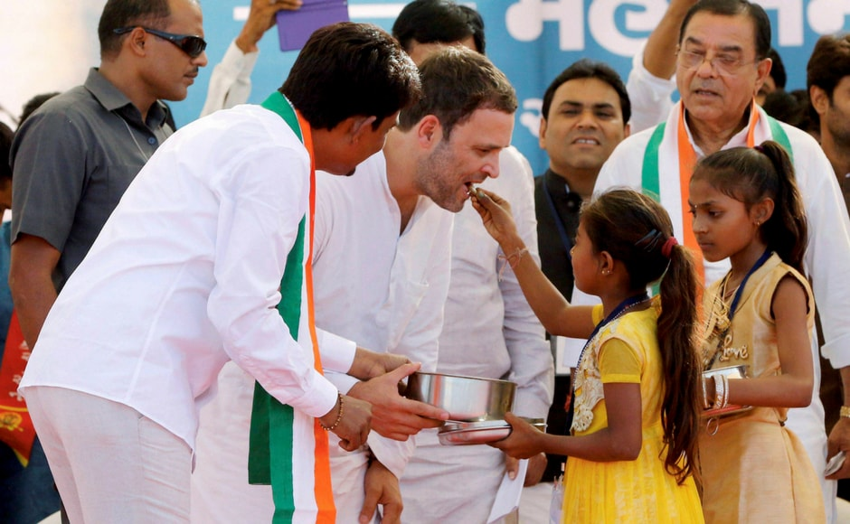 Congress vice-president Rahul Gandhi being offered sweets by children during a public meeting in Gandhinagar, Gujarat on Monday. OBC leader Alpesh Thakor, who joined the party at the rally, is also seen. PTI