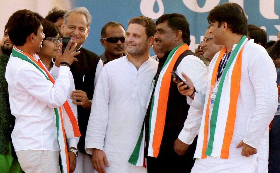 Congress vice-president Rahul Gandhi interacts with the OBC leader Alpesh Thakor who joined the party, during a public meeting in Gandhinagar, Gujarat on Monday. Party leader Ashok Gehlot is also seen. PTI