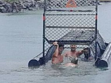 Photo showing a group of men swimming into a baited crocodile trap. Facebook/Stacy W Clayton