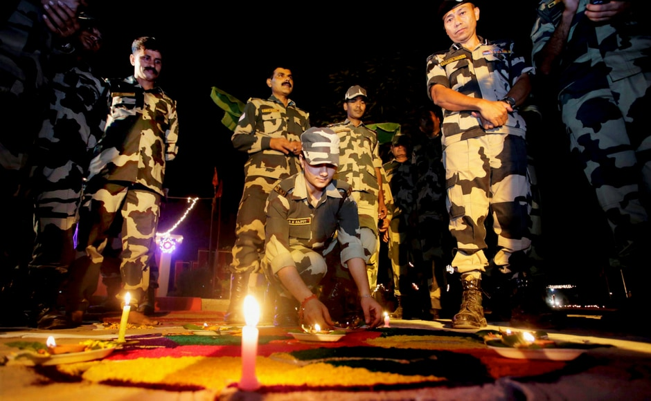 Border security force (BSF) soldiers light candles near the International Border fence at Pargwal about 40 kilometres from Jammu on Wednesday.