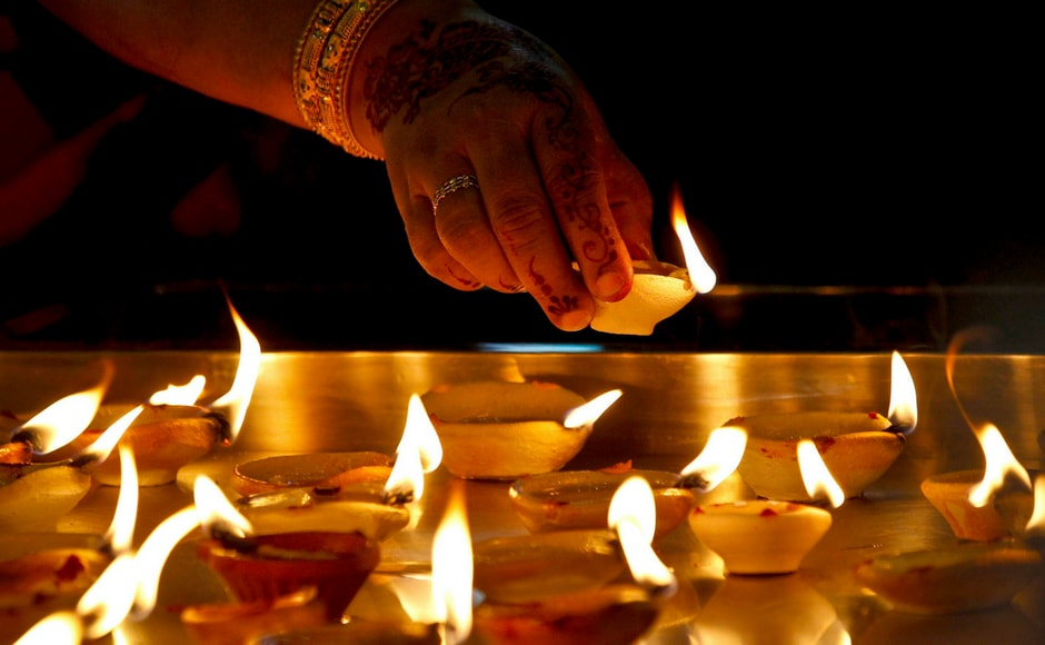A Hindu devotee light up clay oil lamps while praying at a temple during Deepavali celebration in Kuala Lumpur, Malaysia. AP