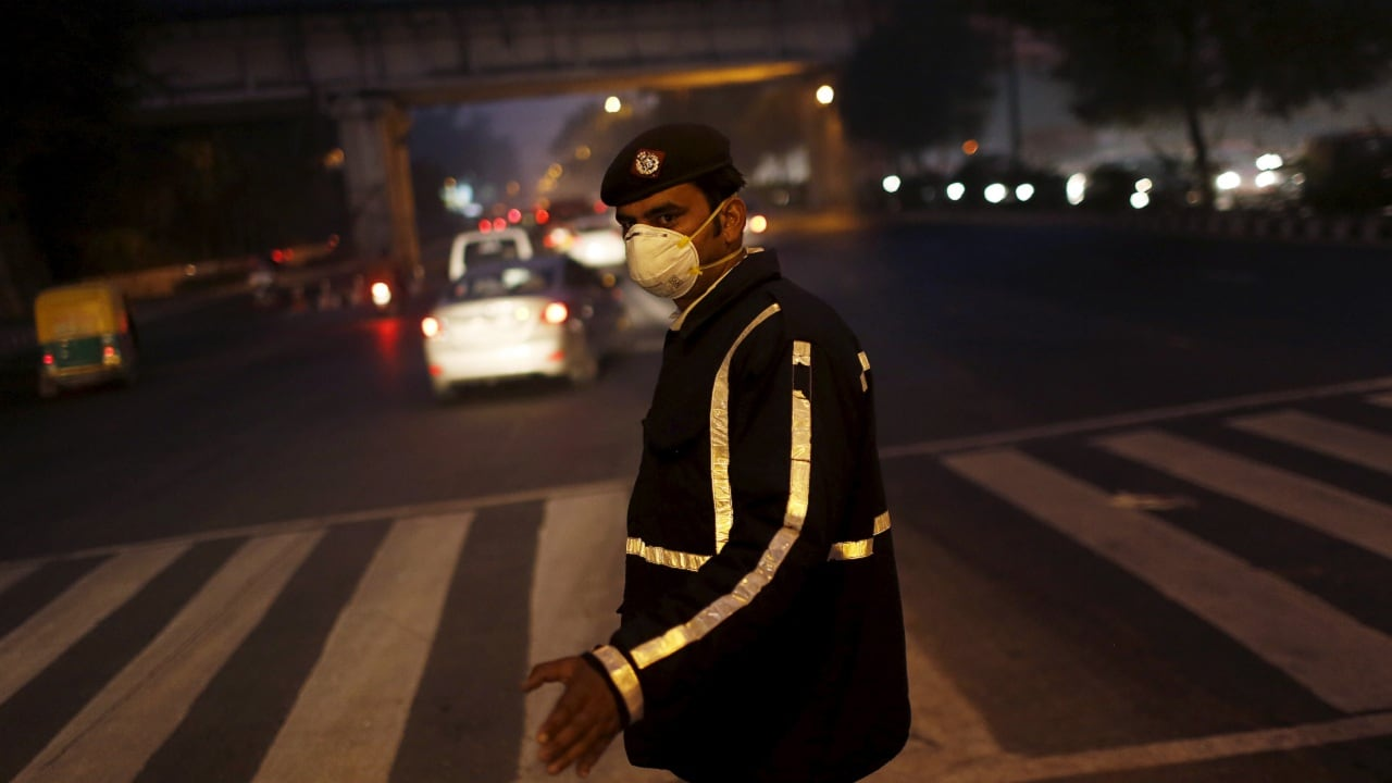 A traffic policeman wears a mask to protect himself from dust and air pollution as he signals to drivers in New Delhi, India, December 23, 2015. India's carmakers and dealers on Thursday called for a clear, nationwide policy to combat air pollution, after a crackdown on diesel cars and trucks in New Delhi, which campaigners have vowed to extend to other cities. REUTERS/Adnan Abidi - GF10000274800