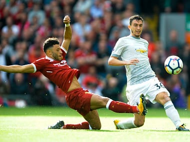 Liverpool's Alex Oxlade-Chamberlain and Manchester United's Matteo Darmian battle for the ball. AP