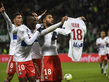Lyon's Nabil Fekir shows his shirt as is congratulated by team mates after scoring against AS Saint-Etienne. AFP