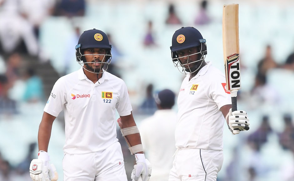 Former captain Angelo Mathews celebrates after scoring a half-century as captain Dinesh Chandimal looks on. Umesh Yadav removed Mathews after he made 52. Sri Lanka end the day with just seven runs behind India's score and six wickets in hand. AFP