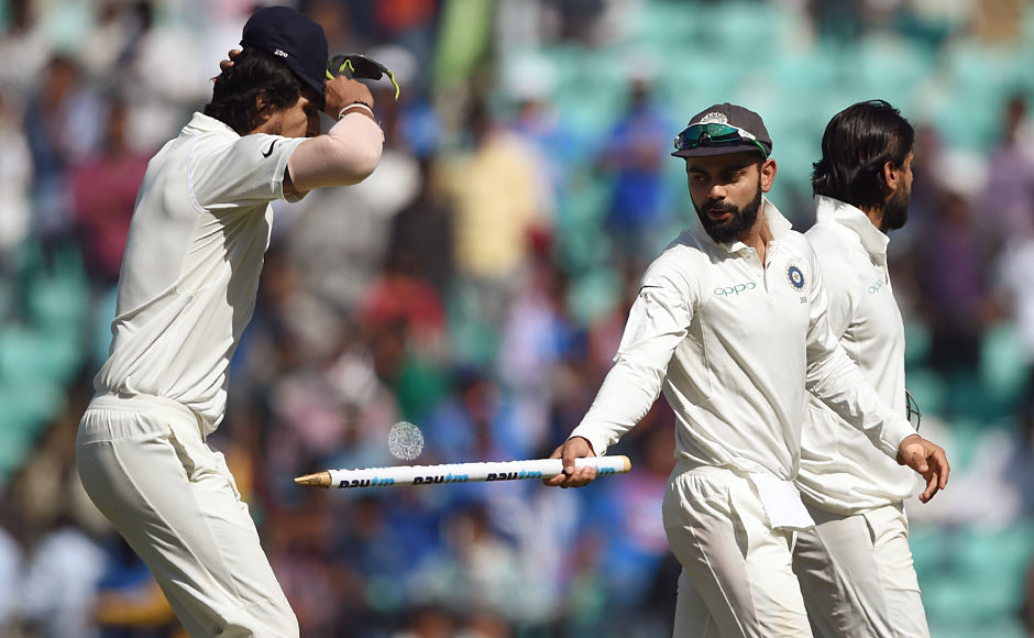 Virat Kohli jokes with Ishant Sharma as they walk back after India won the second Test. AFP